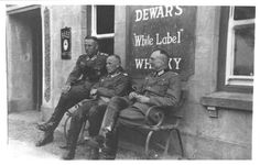 One for the album. A German officer and NCO's relaxing outside a pub on Jersey. Note the Dewar's White Label Whisky and Bass Beer signs.