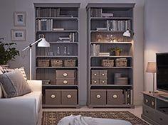 Séjour avec deux bibliothèques grises garnies de paniers et boîtes de différents formats