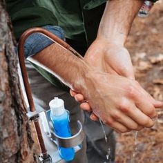 The Advanced Hand Wash System by Tye Works is a portable, hands-free faucet designed for camping that uses a foot operated pump to provide a stream of water from a copper spigot. The advanced model shown here includes a metal bracket that can be used to hold soap or hand sanitizer bottles as well as a towel.