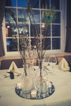 Peacock feathers in antique vases and decanters as the centerpieces