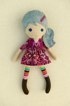 This is a handmade cloth doll measuring 20 inches. She is wearing a dark purple and orange, geometric print dress with a matching, removable skirt, multi-colored, striped leggings, and brown leather boots. Her gray hair is worn in a low, side ponytail and accented with a purple felt