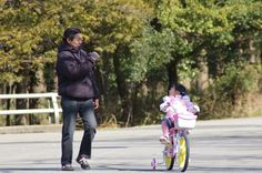 dad films daughter riding her new bike