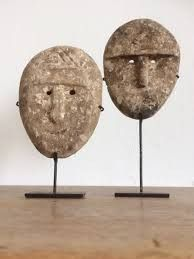 Leuke bijzondere set van twee decoratieve houten maskers op een standaard. Een glimlach in je interieur.
