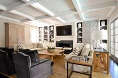 living room with coffered ceiling, neutral furniture and built-ins