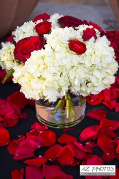 Red roses white hydrangeas on an ivory table cloth with red rose pedals Red Wedding Centerpieces, White Hydrangea Centerpieces, Hydrangea Bouquet Wedding, Red Hydrangea, White Flower Arrangements, Red Rose Bouquet, Wedding Arrangements, White Hydrangeas, Table Arrangements