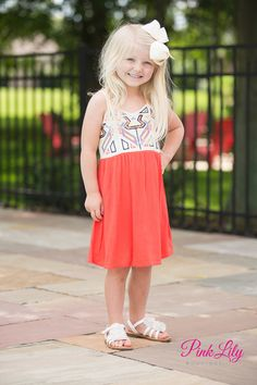 Your child will love this soft and flowy dress! It features bold geometric patterns in black, blue, orange, and yellow paired with an orange skirt.