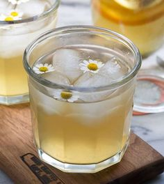 Chamomile Honey and Whiskey Cocktail: Whiskey or Bourbon, Chamomile tea bags, hot water, honey, lemon slices, lemon slices, chamomile flowers for garnish.