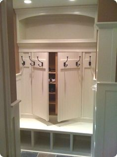 I LOVE this idea for a mudroom. Its got a secret door for storage so you dont see the clutter of shoes and such just thrown all over the floor. Genius!