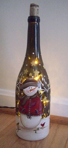 Botella de vino converitda en lámpara pintada con muñeco de nieve