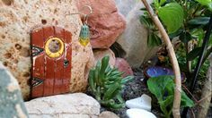 DIY Fairy Garden Door for tree or rock.  Made out of clay. The lantern is a green bead cap with a yellow bead bulb.  The hook is a turkey lacer.