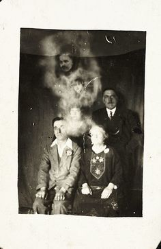 Spirit photography by paranormal investigator William Hope (1863–1933), who used multiple exposure techniques to render the appearance of ghost. Two faces – that of a man and a girl – appear, surrounded in 'mist', above the group. Hope founded the spiritualist society known as the Crewe Circle and his work surged in popularity after the first world war, when many bereaved people were desperate to find evidence of loved ones living beyond the grave.