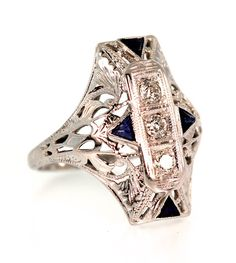 Three Old European cut diamonds with a combined weight of 0.18 carat, average SI2 clarity and H-I color are centered in this 1930's north to south style ring. Accenting the center diamonds are four sy