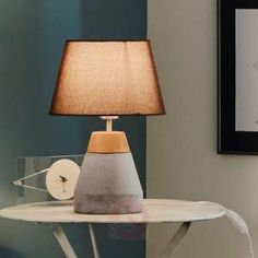 The stand-out feature of the Tarega table lamp is its attractive base, which is made of both wood and concrete. When combined with the dark brown fabric lampshade, it looks both industrial and decorative.