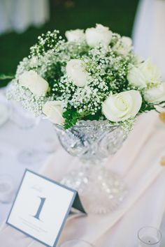 A simple, yet darling, centerpiece of roses and baby's breath #CaliforniaWeddings #WeddingDecorations #Centerpieces