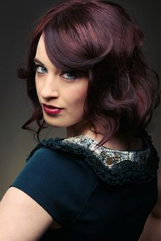 Black hair with mahogany highlights accentuated with swirling side-swept bang.