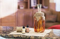 Mason Jar Diffuser  This rustic chic diffuser is a wonderful way to decorate your home, as well as add a pleasing scent!  Ink mason jar. Let dry.    Silkscreen ferns onto the jar according to package directions.    Tie burlap around top of jar and secure with jute.    Add sticks and liquid.