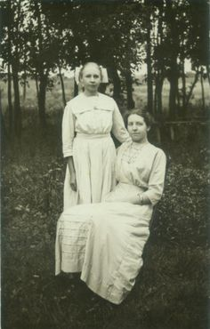 Real photo postcard of two young women friends in field, circa 1910.