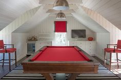 White and red attic game room clad in shiplap features industrial pendants hung above a red pool table placed on a black and white striped rug flanked by red nailhead bar stools and placed in front of a small window dressed in a red and black roman shade located beneath white built in drawers, one fitted with a glass front beverage fridge and one positioned beneath a flat panel television.
