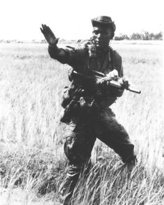 A LRRP team leader, unit D, 1st Squadron, 4th Cavalry, 1st Infantry Division makes it signals his men during a patrol in 1967.