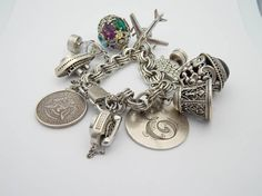 """Sterling silver STATEMENT charm bracelet.  Length is 7"""".  Bracelet is stamped sterling and contains a makers mark.  The ten charms are unique!     1 - 1964 Half Dollar in sterling silver bezel   2 - Sterling silver filigree bell stamped """"sterling DANECRAFT""""  3 - Sterling filigree black onyx scarab stamped """"sterling DANECRAFT""""  4 - Sterling cage with opalescent crystal inside stamped """"sterling""""  5 - Sterling silver filigree ball with large synthetic oval shaped prong set stones - green…"""