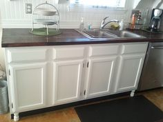 These are builder-grade cabinets! Painted, added black strip beneath, added legs. $24 project. Wow. LOVE!