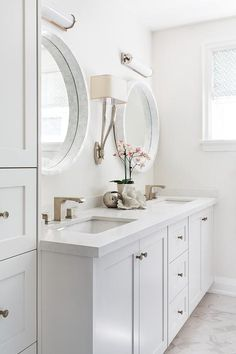 Beautiful light gray bathroom is fitted with white glass sconces lighting two round marble mirrors mounted on a light gray wall on either side of a Ruhlmann Double Sconce fixed above a light gray dual bath vanity accented with a white quartz countertop finished with rectangular sinks and modern satin nickel faucets.