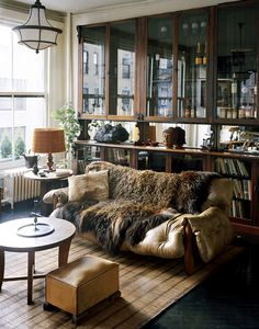 """A slouchy, buffalo-hide <a href=""""https://www.1stdibs.com/creators/sergio-rodrigues/furniture/"""" target=""""_blank"""">Sérgio Rodrigues</a> couch holds pride of place in Alesch and Standefer's living room, atop an <a href=""""https://www.1stdibs.com/furniture/more-furniture-collectibles/rugs/origin/african/"""" target=""""_blank"""">African rug </a>and in front of a vintage <a href=""""https://www.1stdibs.com/furniture/storage-case-pieces/apothecary-cabinets/"""" target=""""_blank"""">apothecary cabinet</a> from…"""