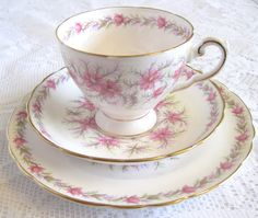 This is a delightfully fresh and feminine set of china by Tuscan decorated with pink flowers and pastel green and lilac foliage. There is a border of the same flowers around the inside of the footed cup and on the plate and saucer which also have scalloped edges. The trio is elegantly trimmed with gold on the rims, foot of the cup and handle. The set is in excellent condition with no chips, cracks, crazing or wear to the pattern/gilding and would be a lovely gift or addition to your chi...