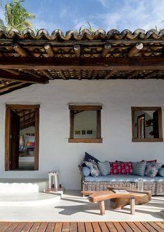 Varanda | O sofá, desenhado por Angela, foi feito em Fortaleza, em um povoado de pescadores. Os estofados foramrevestidos com tecidos da extinta AGain. As mesas de centro de madeira foramfeitas por artesãos de Itaporanga, próximo a Porto Seguro (Foto: Evelyn Müller/Editora Globo)