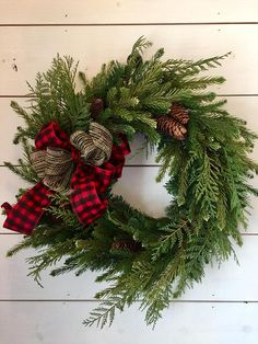 Beautiful FULL faux pine wreath with pinecones. You will not believe it's not real!! I've added a black and red checked flannel bell doubled with a black and tan straw string bow. I think this is going to be my favorite this year! If you prefer a different bow, just message me.