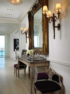 Charming antique furniture pieces grace this luxurious foyer and create a fabulous waiting area.