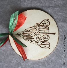 "A unique way to wish someone a Merry Christmas during the winter holiday season, this large round wooden ornament would look lovely on any tree.This unique design, featuring the words of ""Merry Christmas"" in the familiar shape of the tree of the season, has been burned by hand onto a large wooden disc 4"" across, approximately 1/8"" thick. Artist logo, name and year appear on back, as shown.The whole piece is then sealed with a clear acrylic sealant for lasting beauty and ease of care,#zibbet"
