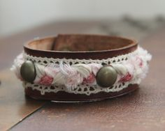 Custom leather cuff bracelet, made out of quality leather, lace, Antique Brass hardware and Pink Braided Fabric. Over all length 8 1/4. Snaps