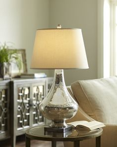 Copley Mercury Glass Table Lamp - This one-light table lamp showcases a delicate mercury glass body topped by a white drum shade. Includes an on/off dimmer switch for adjustable light levels.