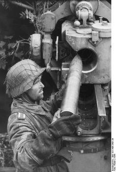 German soldier loading a shell into an 8.8 cm FlaK gun, France, 1944