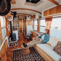 Living Room, Medium Hardwood Floor, Ceiling Lighting, Sofa, and Wood Burning Fireplace Jeffrey hanging in the living area. Bus Living, Tiny House Living, Living Area, Caravan Living, Living Room, School Bus Tiny House, Motorhome, Converted School Bus, School Bus Conversion