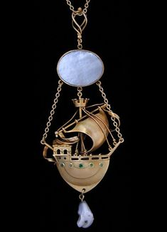 This is not contemporary - image from a gallery of vintage and/or antique objects. LIBERTY & Co.  An impressive, gold, three dimensional, Galleon Pendant with green gem set portholes, surmounted by a pearl moon disc and with a pearl drop.