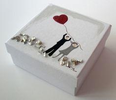 Χάρτινο λευκό κουτάκι μπομπονιέρα γάμου ζωγραφισμένη στο χέρι με ακρυλικά χρώματα και σμάλτο. Εσωτερικά, τοποθετούνται 7 μεγάλα κουφέτα αμυγδάλου σε κόκκινο χαρτί αφής.Υλικό: χαρτί, ακρυλικά, σμάλτοΔιάσταση: 10x10Χ3 εκ. ύψος