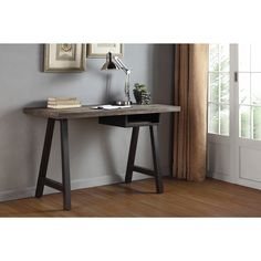 Simple yet stylish, the Renate desk and shelf unit features an unassuming style with a distressed latte-colored desk top mounted on two black-finished A-style legs. A single spacious open shelf finishes the look of this practical desk.