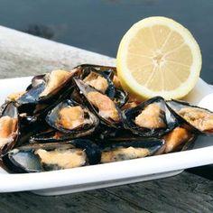 Grilla färska musslor på engångsgrill. Dela musslorna när de öppnats, pensla med vitlökssmör och värm dem på grillen en kort stund till.