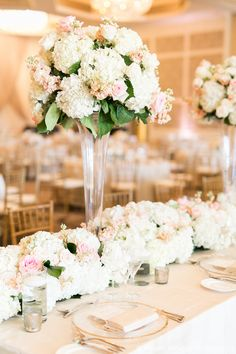 head table at reception featured tall lush arrangements of white hydrangea, peach stock, and ivory, peach and blush roses, interspersed along a full flower table runner of white hydrangea, ivory, peach and blush roses, peach stock and lemon leaf.