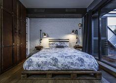 une chambre à coucher de style industriel et d'esprit loft avec un grand lit palette effet bois de grange