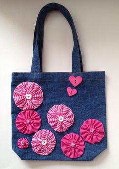 This whimsical denim tote features pink & striped hand sewn yo-yo flowers accented with teeny-tiny yo-yo & white button centers. It is also adorned with 2 cute heart-shaped novelty buttons, making it ideal for Valentines day gifting. The tote is cotto Denim Handbags, Denim Tote Bags, Diy Bags Purses, Denim Crafts, Jute Bags, Patchwork Bags, Girl Gifts, Wallets For Women, Bag Making