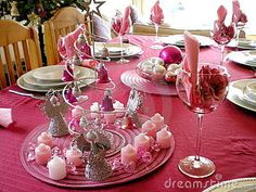 A colorful laid table decorated different in pink with xmas decoration for a christmas dinner in the dining-room indoors at home