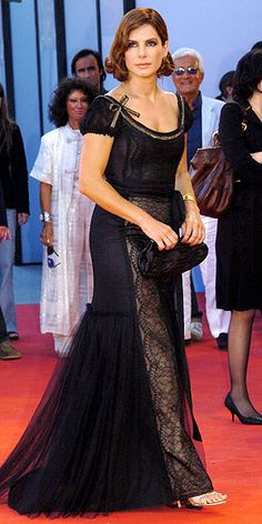 Sandra Bullock's Style Evolution | SHORT AND SWEET   | Remember Sandra with short hair? Here's a photo to jog your memory. The year was 2006, and she paired her wavy bob with a cap-sleeve black gown at the Infamous premiere during the Venice Film Festival.