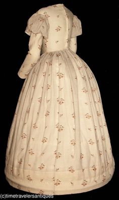 A very lovely original circa late 1830's lady's floral printed cream silk challis one piece gown that is a wonderful example of a transitional style. The bodice is lined ans stayed, with a fan pleated front, piped at all the seams, with fashionable slender capped sleeves, a two part back with a blind hook and eye closure, a cartridge pleated waistband, and an unlined skirt with a deep turned and faced hem.