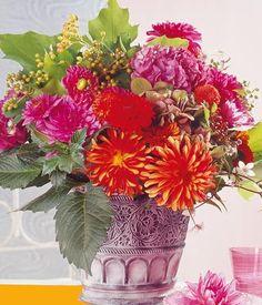Die Pop-Prinzessinnen des Herbstes trumpfen in der Vase so richtig auf – Dahlien und Hortensien in Rot, Orange und Pink.