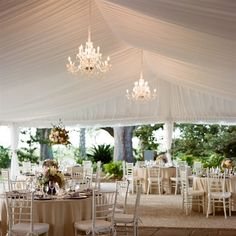 Tented garden reception with champagne linens and white chairs. Envision slate grey napkins at the tables