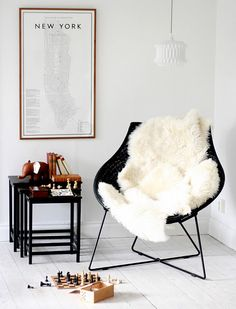 ikea sheepskin rugs on chair for bedroom corner. Makes it looks modern but comfy!