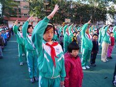 """China - Elke maandagochtend staan de leerlingen van deze school op het schoolplein om de Chinese vlag te groeten. De rode sjaaltjes lijken uit de rode Chinese vlag te zijn geknipt en beteken dat alle kinderen een stukje van het grote land China zijn. Elke oudere leerling leert dat aan een jongere leerling, net als de eed: """"Ik beloof onder de vlag dat ik van mijn vaderland houd en van het volk. Ik zal goed leren en zorgen dat ik fit blijf. Ik sta klaar om mijn deel bij te dragen aan het…"""